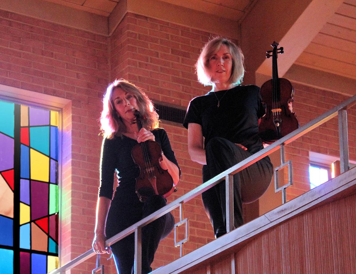 Margie Heath and Jill Farmer from Jolie Deux Violin Duo stand