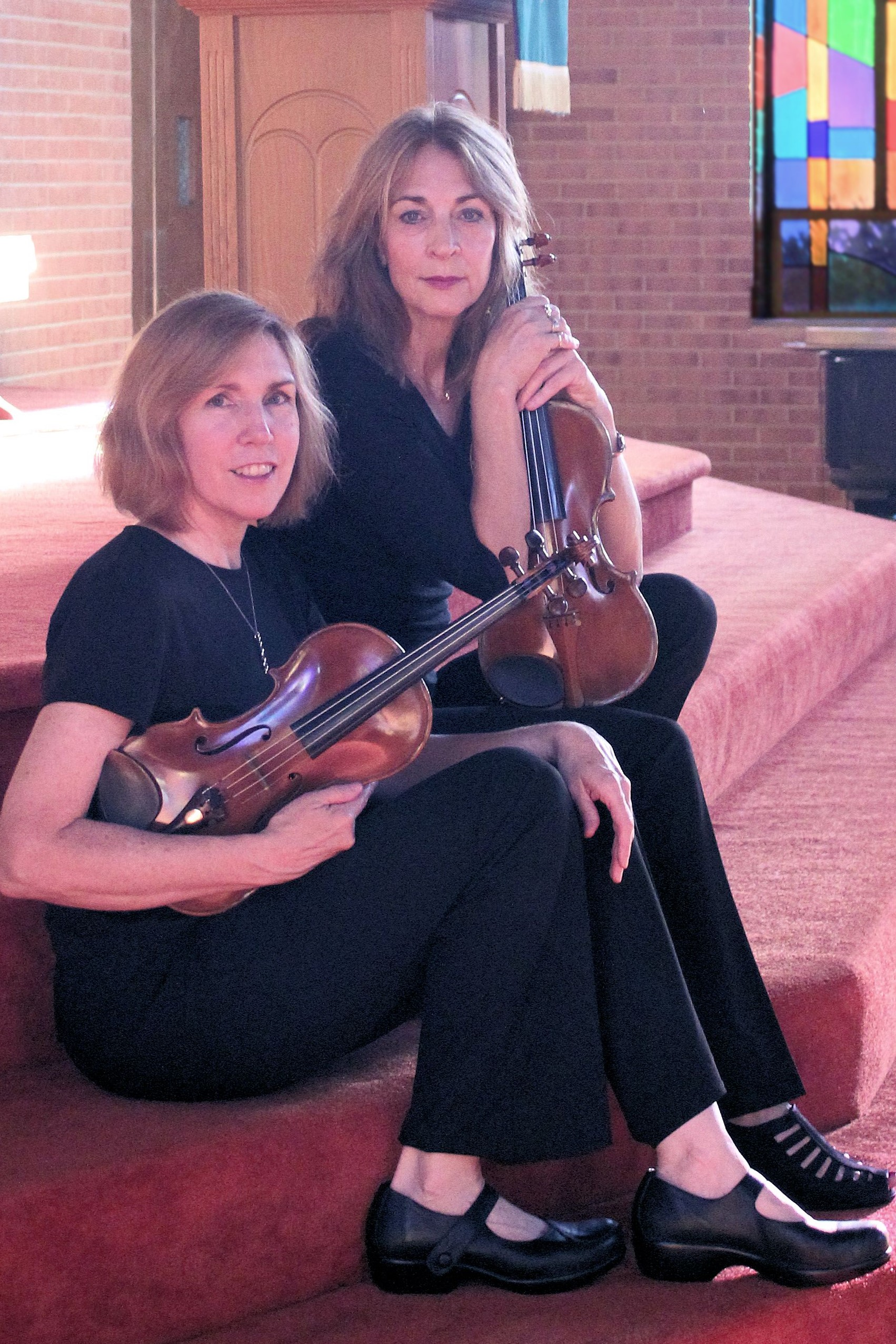 Margie Heath and Jill Foster from Jolie Deux RVA violin duo sitting on steps
