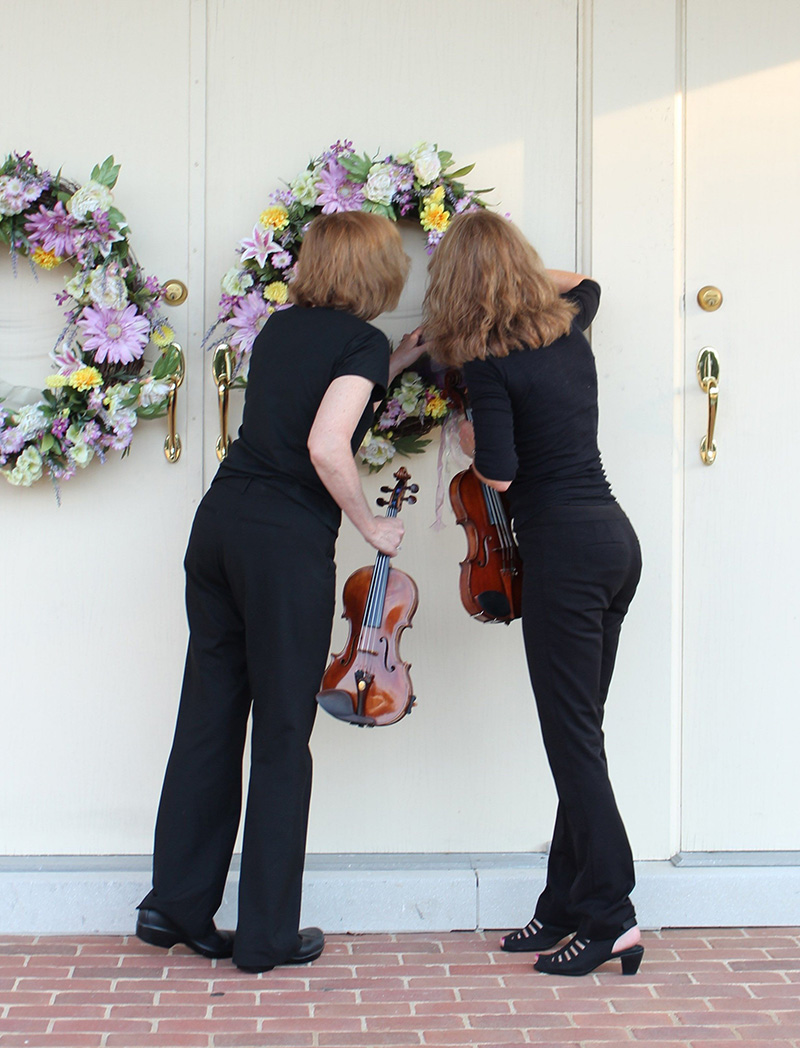 Members of Jolie Deux RVA Violin Duo looking at wreaths on church door