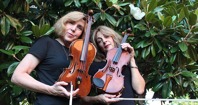 Contact Jolie Deux: Jill Foster and Margie Heath from Jolie Deux RVA violin duo holding violins in front of magnolia